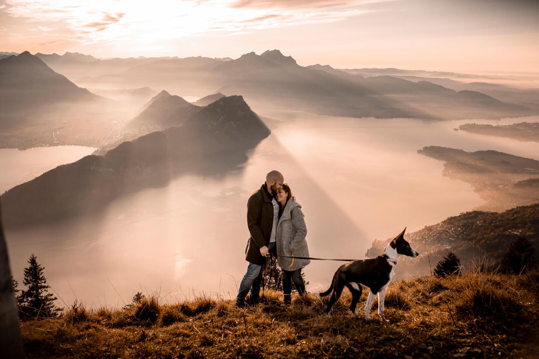 Ein Paar steht zusammen mit einem Podenco Hund auf einem Berggipfel. Im Hintergrund ist der Vierwaldstättersee, der Bürgenstock, das Stanserhorn und der Pilatus. Ein oranger Sonnenuntergang.