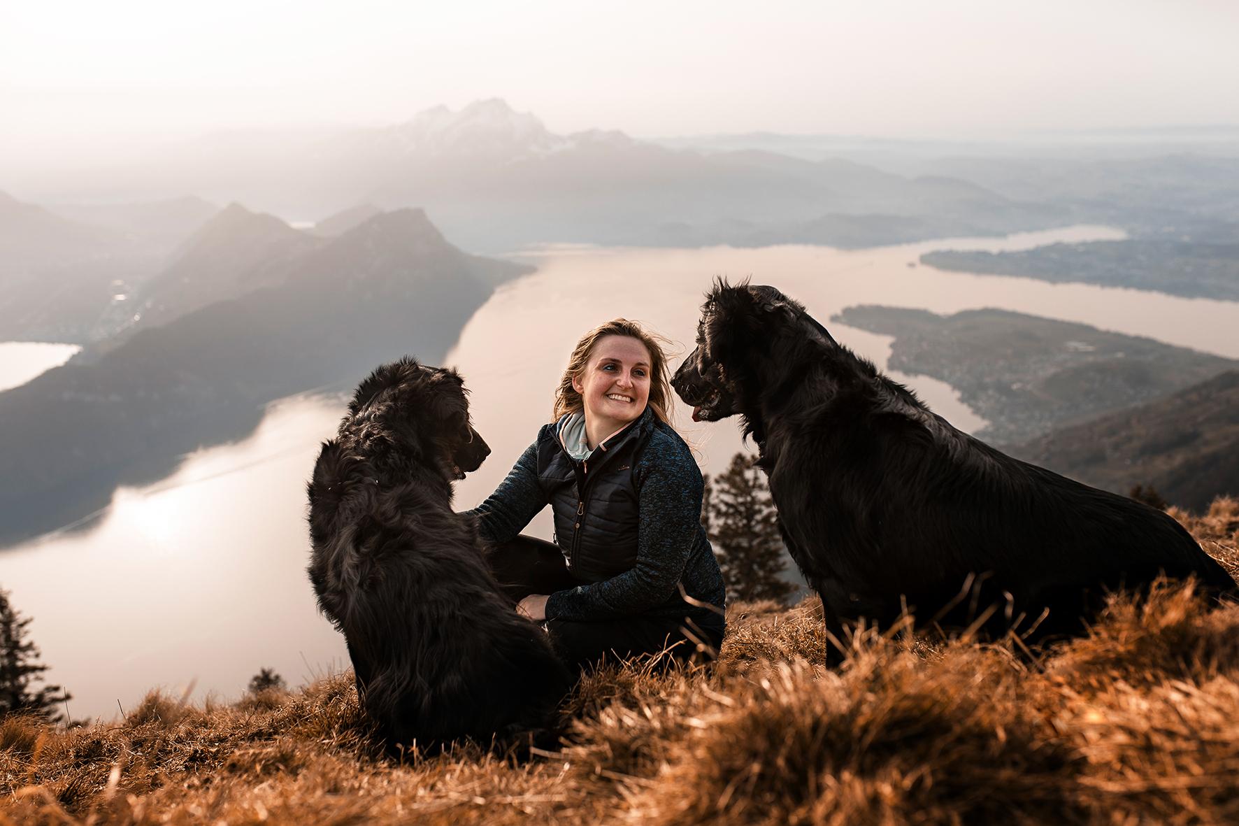 Zwei Flatcoated Retriever Hunde und eine junge Frau sitzen für ein Hundeshooting auf einem Berggipfel. Im Hintergrund ist der Vierwaldstättersee, der Pilatus, der Bürgenstock und das Stanserhorn zu sehen.